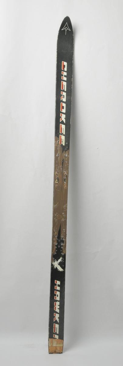 Alpinski laga av glasfiber. Svart overside med emblem i tupp og motiv av hauk nede på skia. Svart plastsåle med stålkantar. Forsterka med ståltupp. Det har vore bora ei mengde hol i skia på midtpartiet.