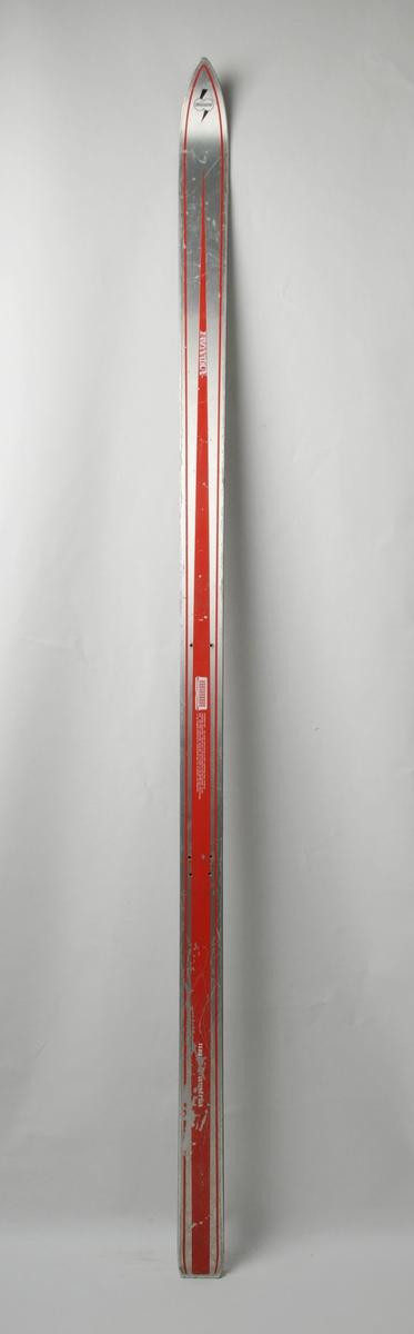 Alpinski laga av glasfiber, med overflate av aluminiumslegering. Plastsåle med stålkantar. Metallic overside med raud dekor.