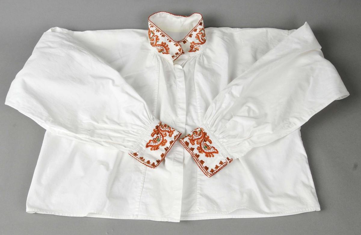 Skjorte i primærsnitt med kulørt rosesaum på hals- og armliner. Heil opning i front. Armane er rynka ved linene. Lask under armane, tre legg på kvar side av armpåsettinga. Kanting av krage og armliner med hemper sydd med knappholssting.