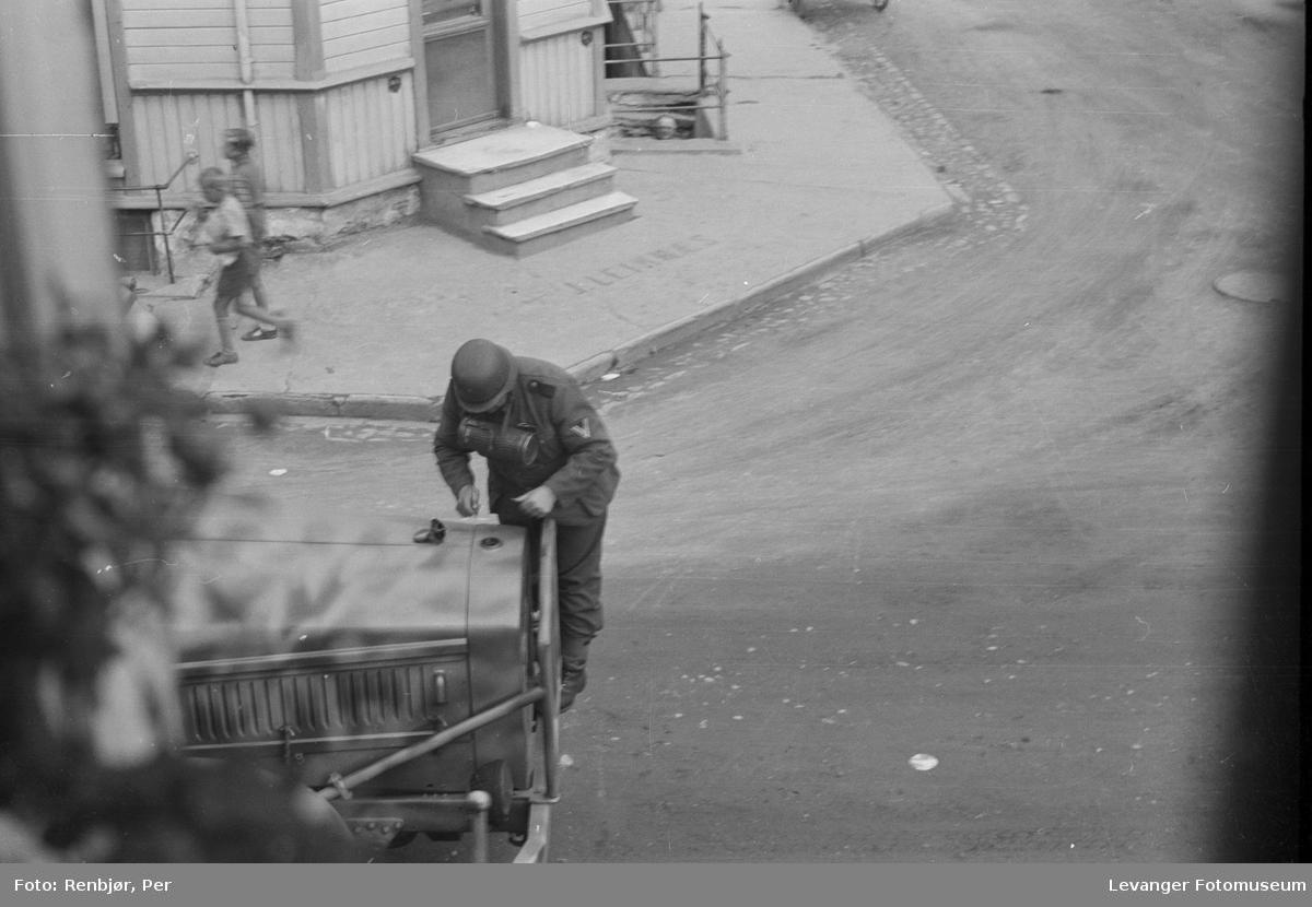 Tysk soldat sjekker radiatoren på lastebilen i Levangers gater.