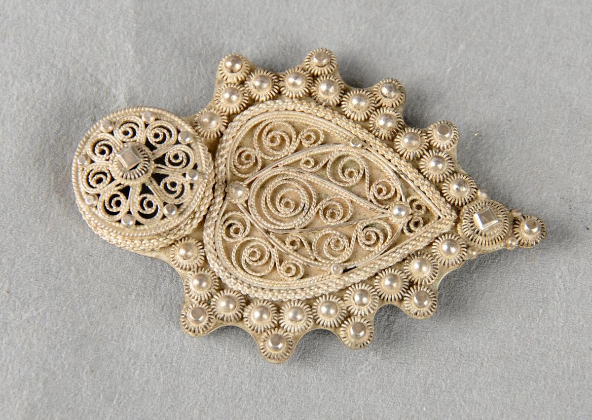 Eine delen av kassert trøye- eller jakkespenne. Hjarteforma, filigransarbeid.