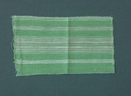 Randigt möbeltygsprov i grönt, oblekt och brunt, vävt i korskypert med bomullsgarn i varp och lingarn i inslag.