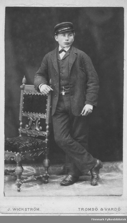 Ung mann helfigur portrett står med kryssa bein, armen lent på en stolrygg. Han har en lue hatt og dress, hvit skjorte og sløyfe. Studio ateliere.  Albumet med bildet kommer fra Ekkerøy, kanskje han bodde der.