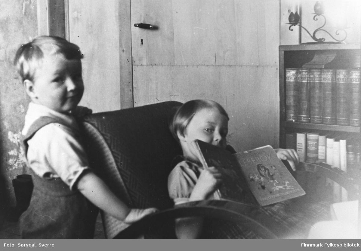 Eirik og Randi Sørsdal i Syltefjord. Jenten sitter i en stol og ser i en bok mens gutten står ved siden av. Ved siden av stolen står en bokhylle og vi se døra i bakgrunnen.