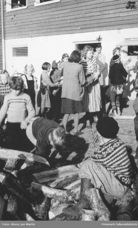 Vedforsyning til vinteren ble levert til Øksfjord barneskole, og alle elevene måtte hjelpe til med å bære veden i hus. Læreren ved døra het Halfdan Ørstavik