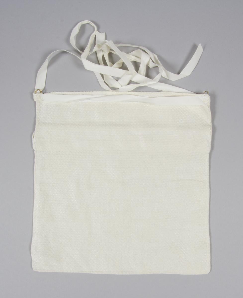 Kjolsäck till dräkt för kvinna från Mora socken, Dalarna. Modell med avskuret framstycke. Tillverkad av handvävt linnetyg, vävt i sålldräll. Breda fållar i överkanterna. I bakstyckets överkant sitter två hyskor av mässingstråd. Ett fabriksvävt band av vit bomull är fastsytt i närheten av hyskorna.