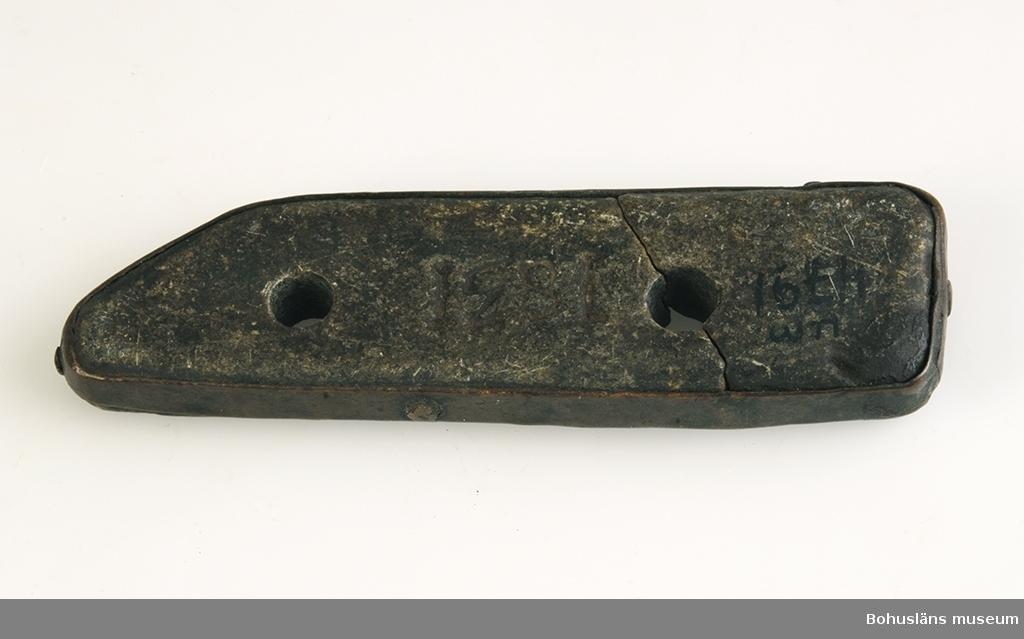 """Ur handskrivna katalogen 1957-1958: Sten för tillverkning av hagel """"1831"""" L. 11,5 Br. 3. Knivbladsformad sten inramad av metallband. Stenen sprucken.  Lappkatalog: 55"""