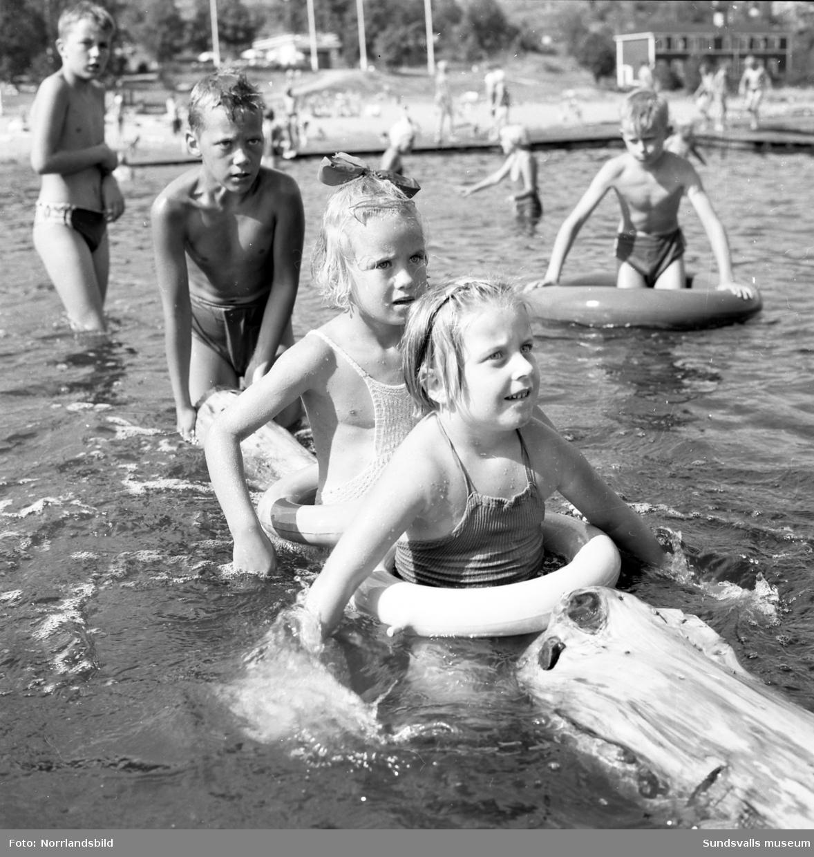 Semesterliv vid Fläsian. Badande barn och grabbar som spelar minigolf.