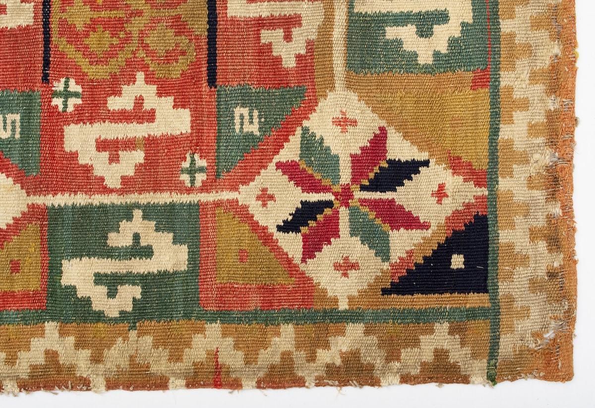 Åkdyna vävd i rölakan, hel- och halvstygn. Motivet framställer två trädformer, små och stora S-former (rättvända och spegelvända) inskrivna i två åttkanter. Spetsuddiga stjärnor med åtta skarpt markerade vingfält. Runt om löper en sicksack-bård . Åttkanternas bottenfärg är gulröd, mönster i två nyanser grönt, rödblått, blått, gult, vitt, brunrött och gulbrunt. Kortsidorna är fållade.   Varp i s-tvinnat lingarn, 4 trådar/cm. Inslag i 1-trådigt s-spunnet ullgarn, 2-3 trådar tillsammans, 15 inslag/cm. Spår av fjäder. Spår av lingarn längs långsidorna.