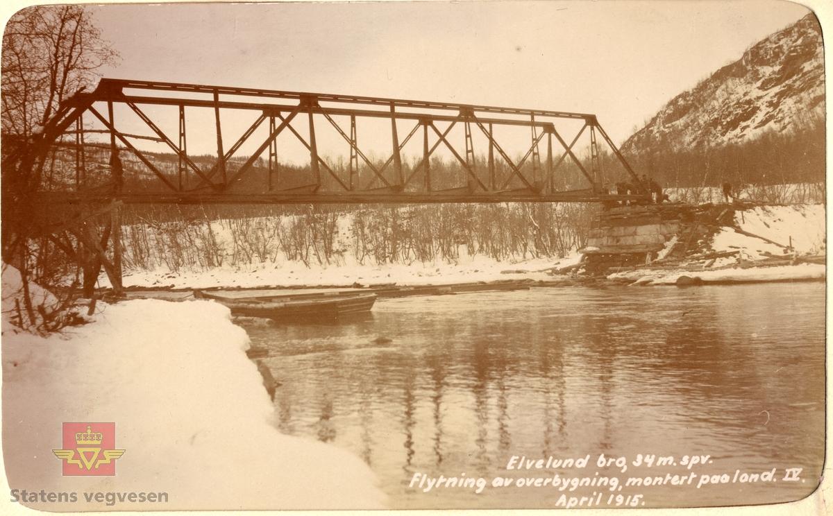 """Elvelund bru i Sørreisa, Troms, under bygging . April 1915. Spennvidde er 34 meter. Brua er blitt satt på plass etter at stålkonstruksjonen er trukket over elva, ved hjelp av stillaser.  Tekst på bildet: """"Elvelund bro. 34 m. spv. Flytning av overbygning, montert paa land (IV). April 1915"""""""