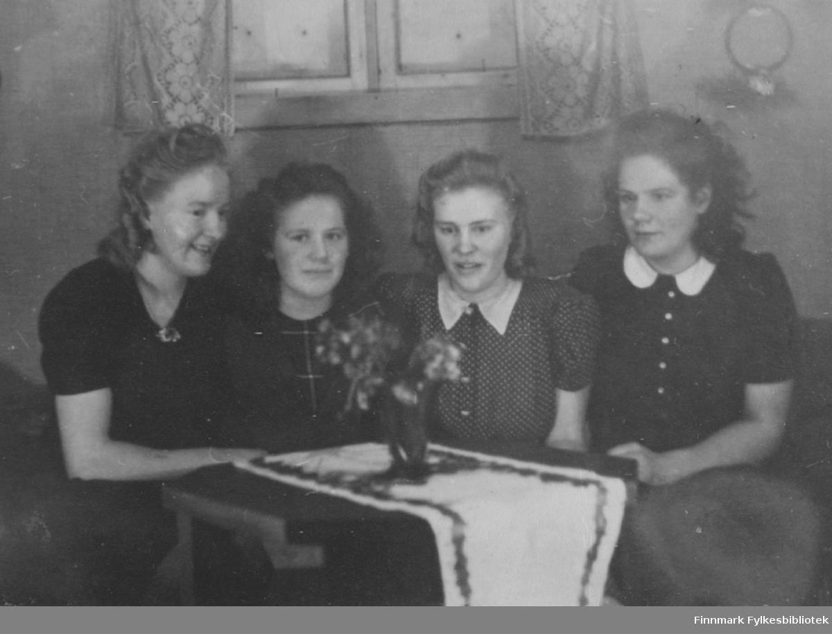 Fotografi av fire kvinner som sitter rundt et bord. Fra venstre Ågot Jakkola, Agnes Randa, Helga Sørensen og Laila Berg. Alle er født Stenbakk. Laila og Agnes var søstre. Det var også Ågot og Helga. Kvinnene var kusiner. Bordet er pyntet med duk og en vase med blomster. Oppe på veggen bak kvinnene er der et vindu med gardiner