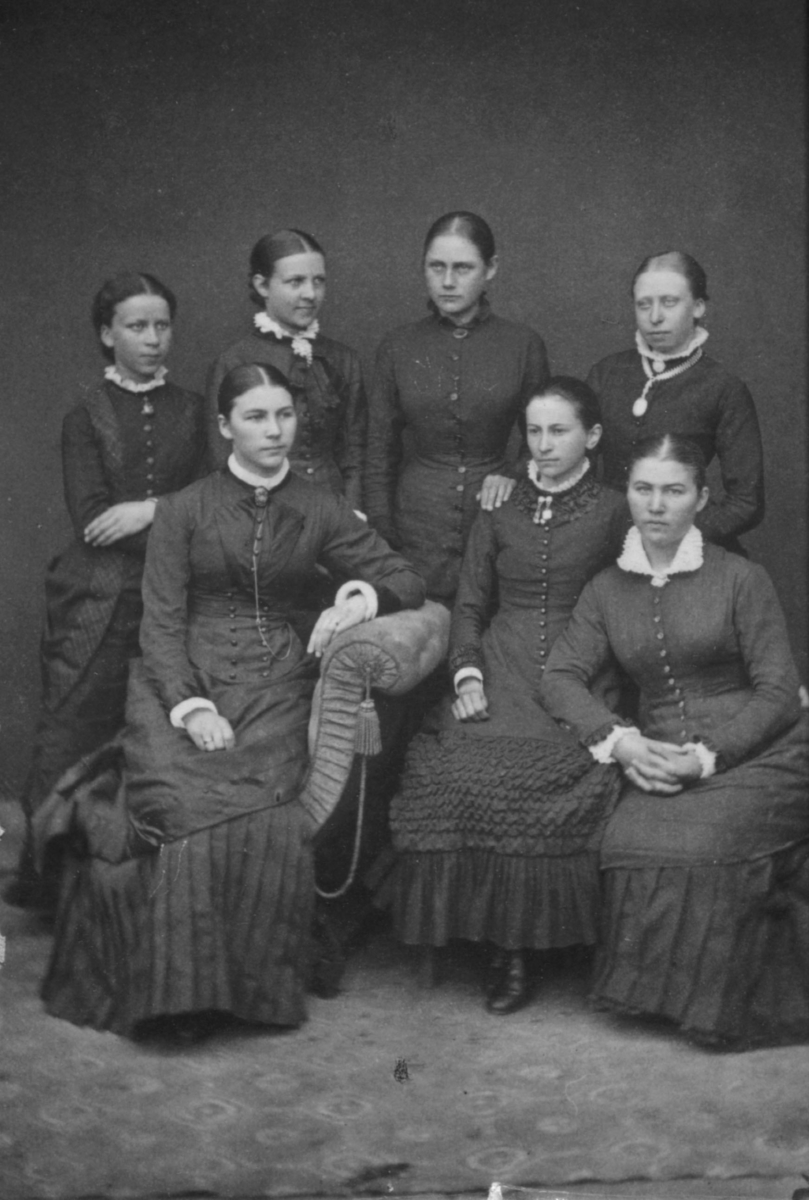 Gruppeportrett av sju unge kvinner, fotografert i atelier
