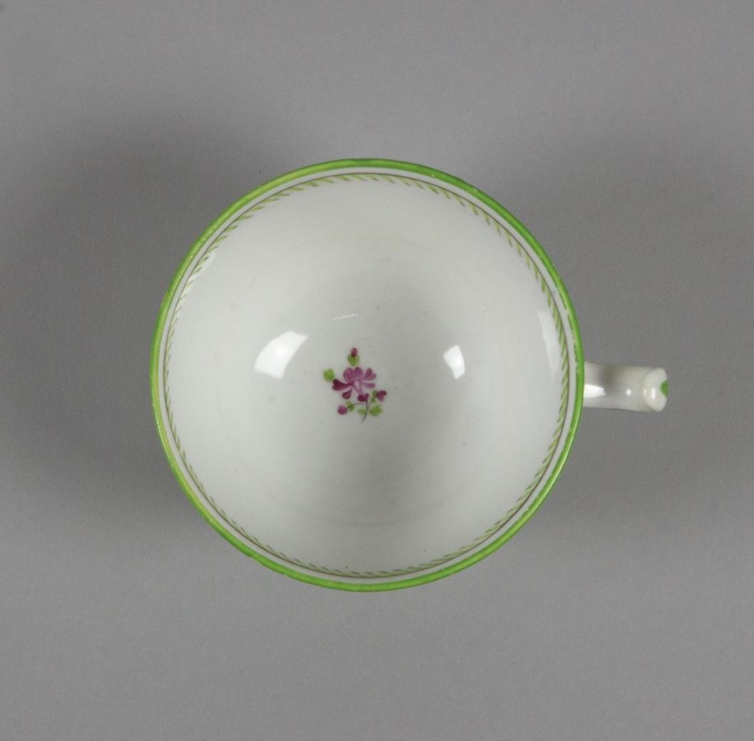 Kaffekopp av vit fältspat. Skålform med fot, dekorativt utformat öra. Målad dekor på glasyren, strödda fantasiblommor i två lila toner, grönt och grått. Några prickar i leran och glasyren.