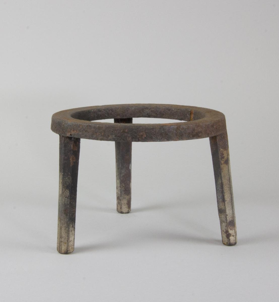 Trefot gjuten av järn. Med platt ring av järn på tre nedåt avsmalnande fötter.