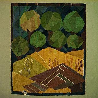 """Bildväv med motiv av åkrar i olika växtstadier, träd och himmel. En åker är nyplöjd, två är ännu inte skördade och en är fortfarande grön. Träden i många gröna nyanser avtecknar sig mot en djupblå himmel. Varp av lingarn och inplock av ullgarn. Monterad med langettkant och orientalisk fläta. Kanal med träpinne i i ovankanten. Märkt i nedre högra hörnet """"KM""""."""