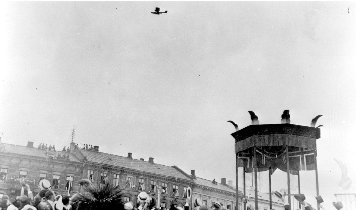 """Luftfoto, ett fly i luften, Dornier-Wal, """"N-25"""".over Oslo. Folkemengde på bakken under."""