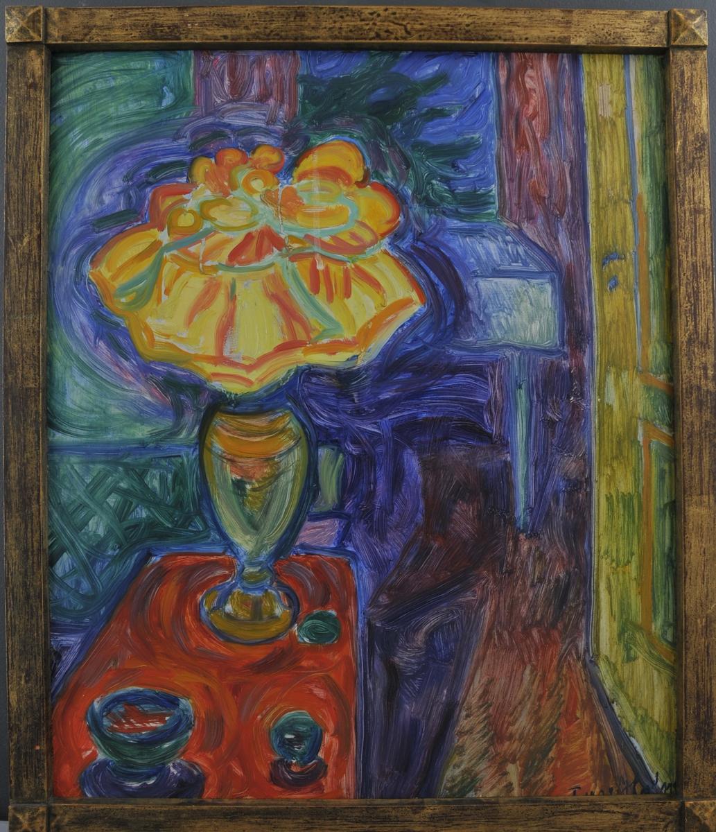 Interiør, med eit bord i framgrunnen med gule blomar i ein blomstervase, oppå.