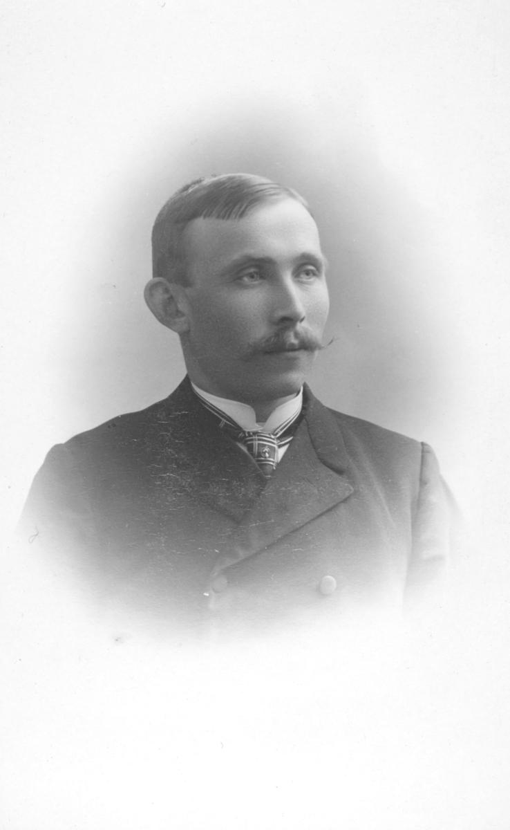 Portrett fra en ukjent mann med stor snurrebart (vokset) og kledd i dobbeltspent dress, skjorte og slips.
