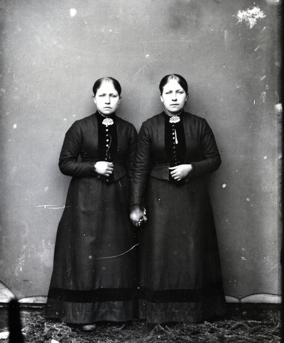 To kvinner i helfigur som holder hverandre i hendene. Stående foran lerret. Mørke, fotside kjoler