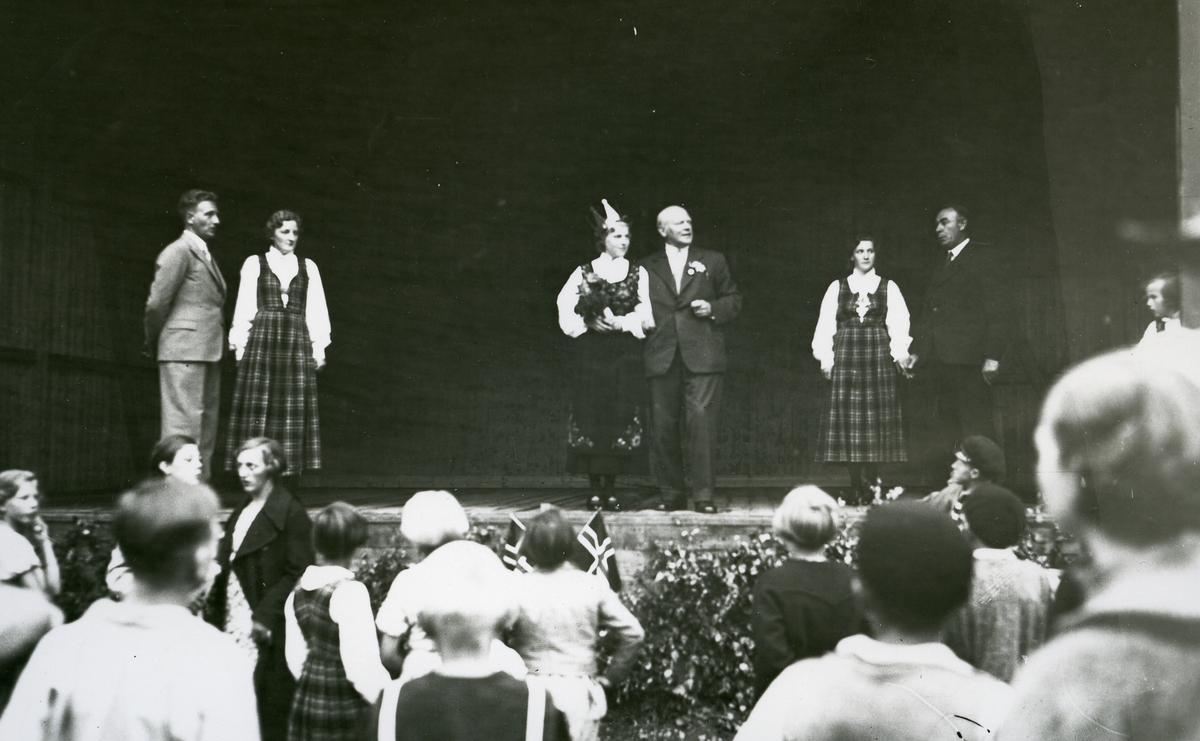 Tre kvinner og tre menn på scena på forsamlingshuset Folkvang. Kvinnene i rutastakk og valdresbunad. Kåring av Valdresprinsesse
