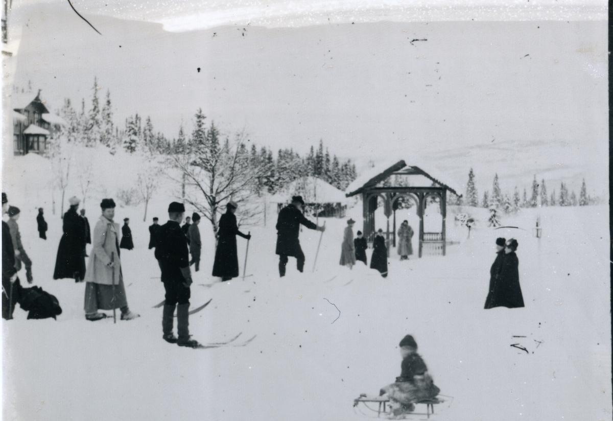 Turistar på Tonsåsen sanatorium, med ski og kjelkar. Bygning til venstre og paviljongar i sveitsarstil