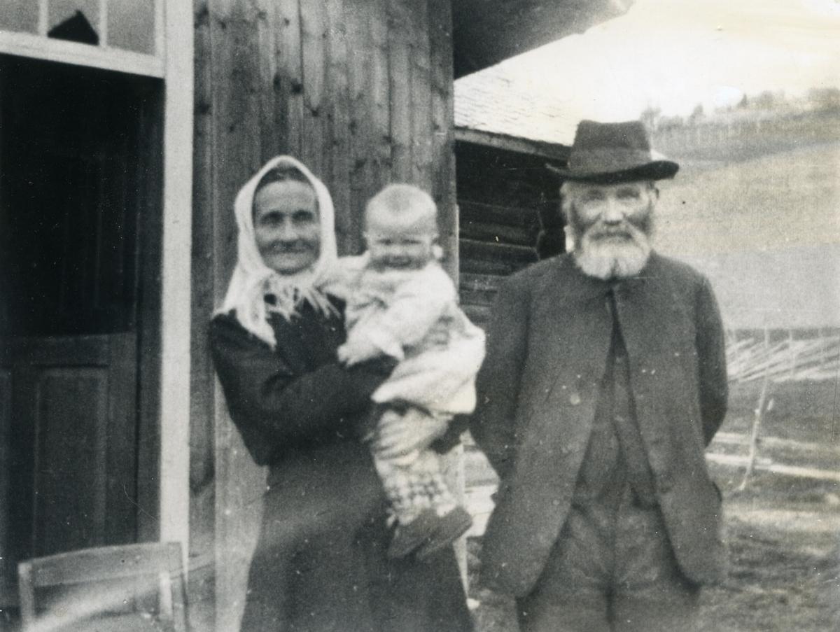 Eldre mann og kvinne framfor bygning, ho med eit born på armen. Livaursfolket i Nørre Haugen i Skrautvål