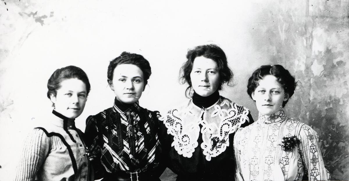 Fire kvinner avbildet foran lerret.