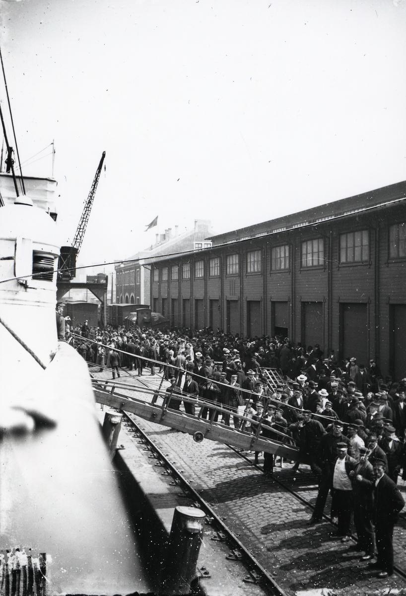 Båt ved kai i Gøteborg. Mange mennesker på kaia. Utvandring?
