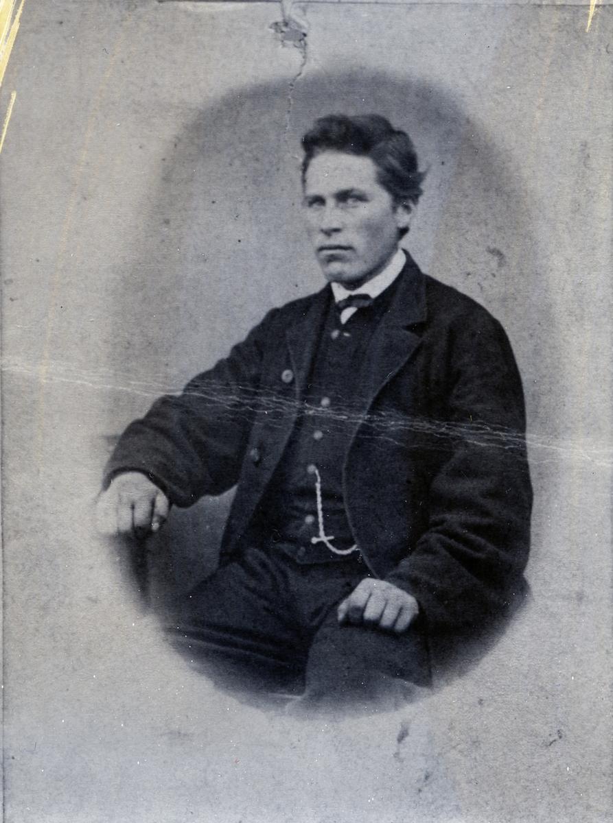 Ung mann avbildet i halvfigur, sittende. Ola Nerby, født på sørre Grøv, Hedalen