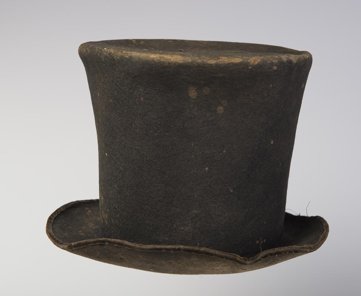 Filthatt med høy stiv pull som er flat på toppen.  Rundt ytterkanten av bremmen er det påsydd et smalt fløyelsbånd. Papir i toppen av pullen. Øvre del av hatten har større omkrets enn lenger nede. Denne type hatt er forløperen til flosshatt.
