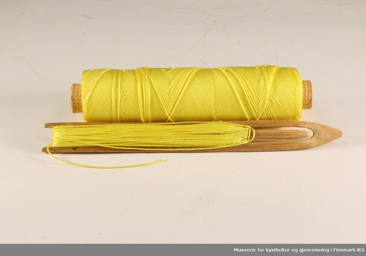 Garnnål av tre med gul tråd og trådsnelle. Brukt til å sy og reparer fiskegarn.