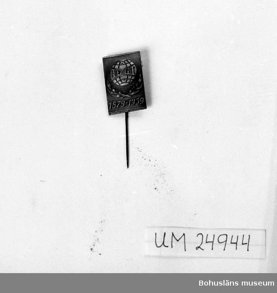 """Fyrkantig. Jordglob med utmärkta longituder och latituder. Lagerblad under globen. Text på globen: """"IOGT"""". Text under globen: """"1879 - 1939"""". Text på baksidan: """"WAS WESTINS ATELJÉ STOCKHOLM""""."""