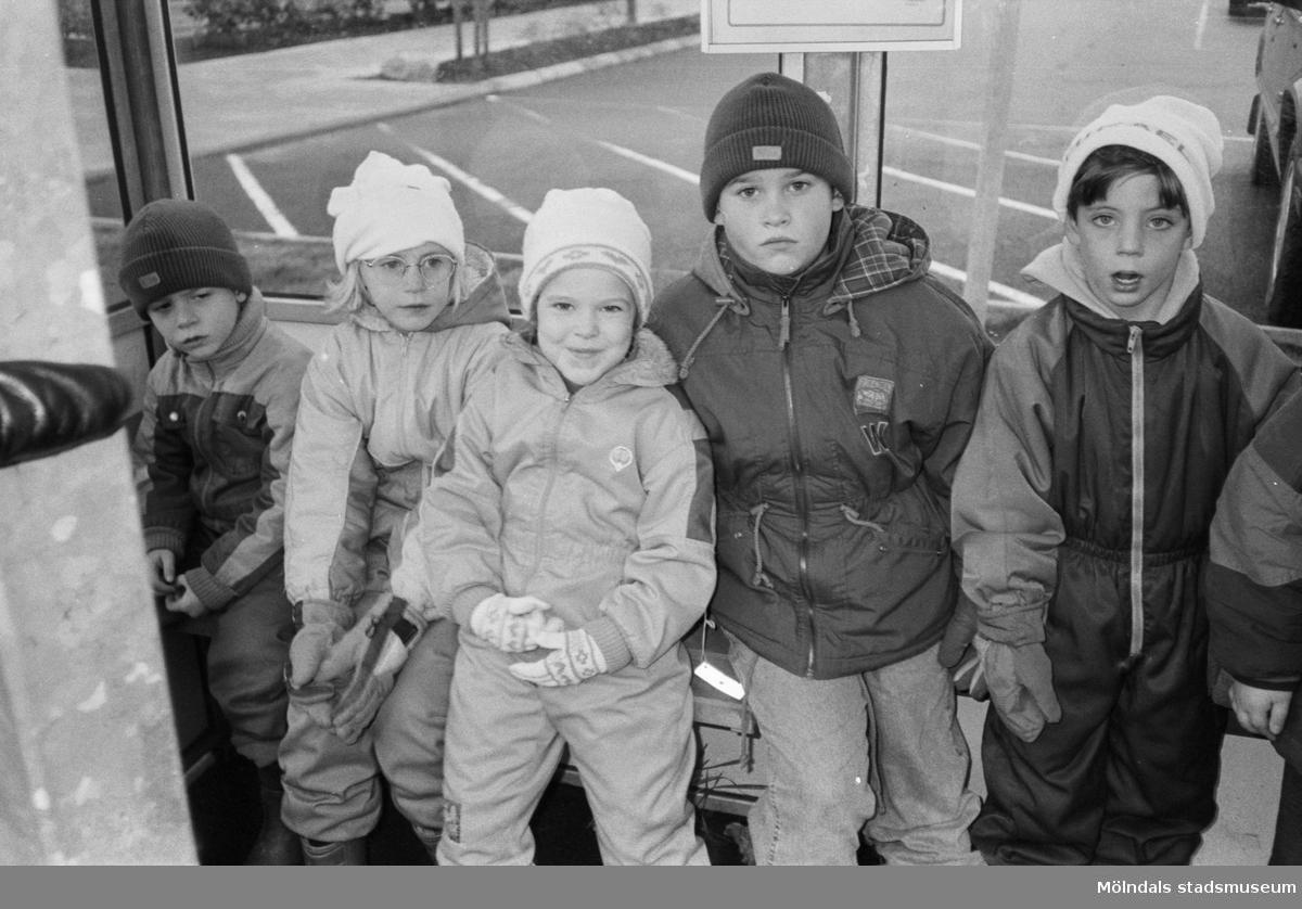 Fem barn, iklädda jackor, mössor och vantar, sitter/står i en busskur. I bakgrunden syns tomma parkeringsplatser. Utflykt med Katrinebergs daghem, 1992.