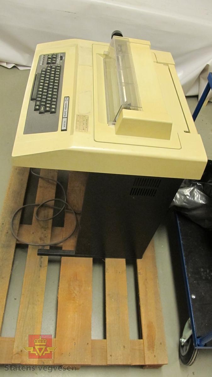 Beige terminal på svart ramme. Terminalen er intakt men bærer preg av å ha stått en stund. Det er også flere klistremerker som har falt av eller har blitt fjernet. Tastaturet er grått med et lite instrumentpanel på venstre side der man kan stille inn print.  På undersiden av rammen sitter det sikringer og maskinens strømledning.  Toppen av terminalen kan åpnes for å skifte printerkassett og lignende. Ellers er terminalen i god stand.