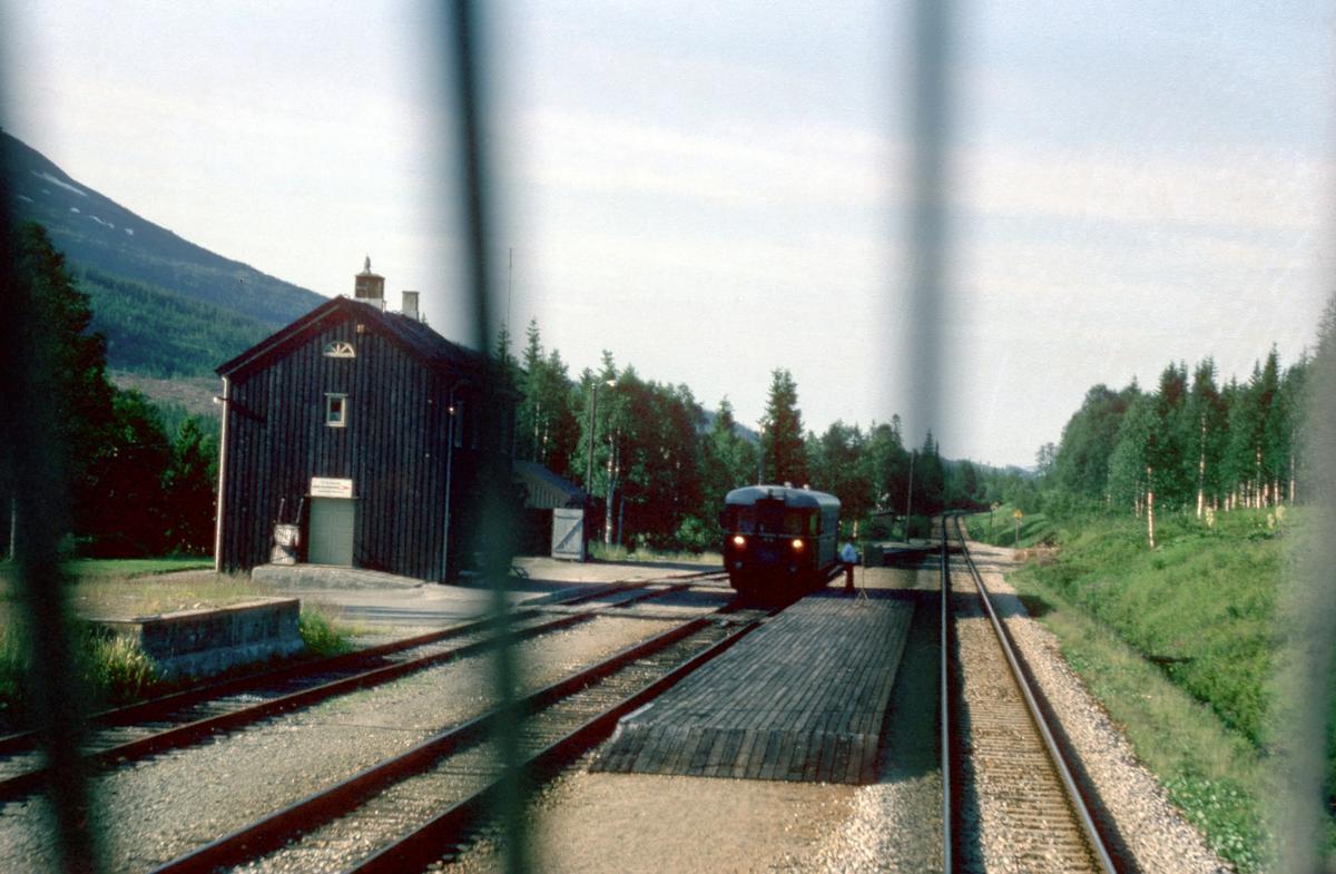 """Togekspeditøren i Svenningdal viser signal """"Passer"""" (grønt flagg) til lokomotivføreren i godstog 5794. Toget krysser med tog 475 """"Majavassvogna"""", Majavatn - Mo i Rana."""