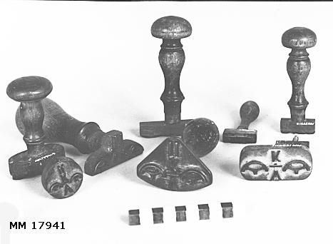 Stämplar av mässing, vissa gängade till träskaft. Olika format, samtliga försedda med kronostämpel, typ kattfot på vardera sida om bokstäverna. Spår av röd färg. MM 17941.4 (är en gummistämpel). : V K