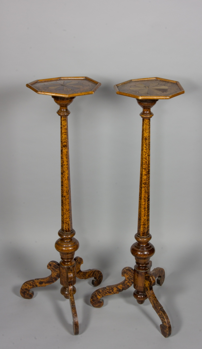 Geridonger, 2 st, tillverkade av alrot med 6-kantigt ben och tre volutformade fötter. 8-kantig plan skiva med inlagda bladformer i olikfärgad fanér.