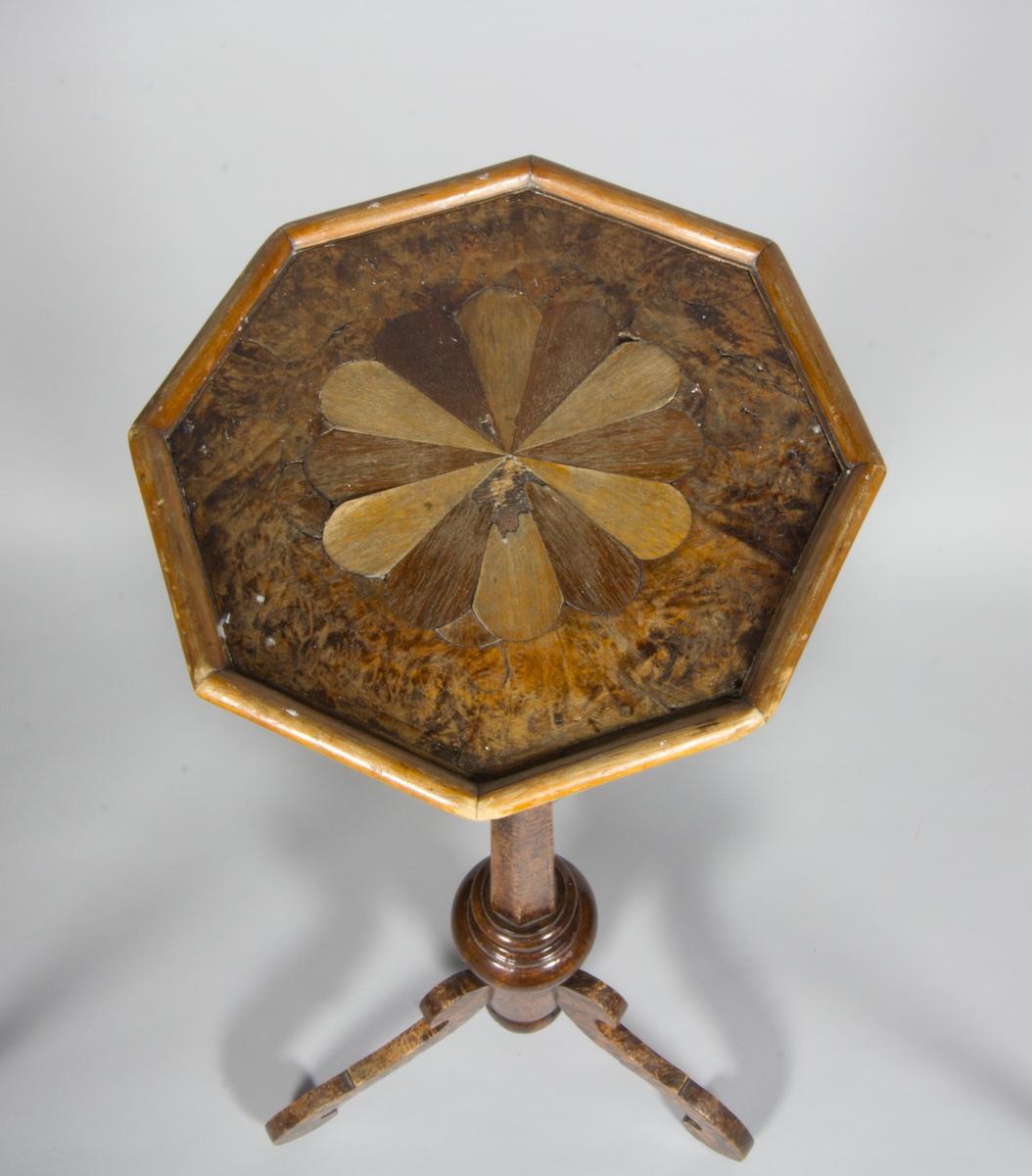 Geridong tillverkad av alrot med 6-kantigt ben och tre volutformade fötter. 8-kantig plan skiva med inlagda bladformer i olikfärgad fanér.