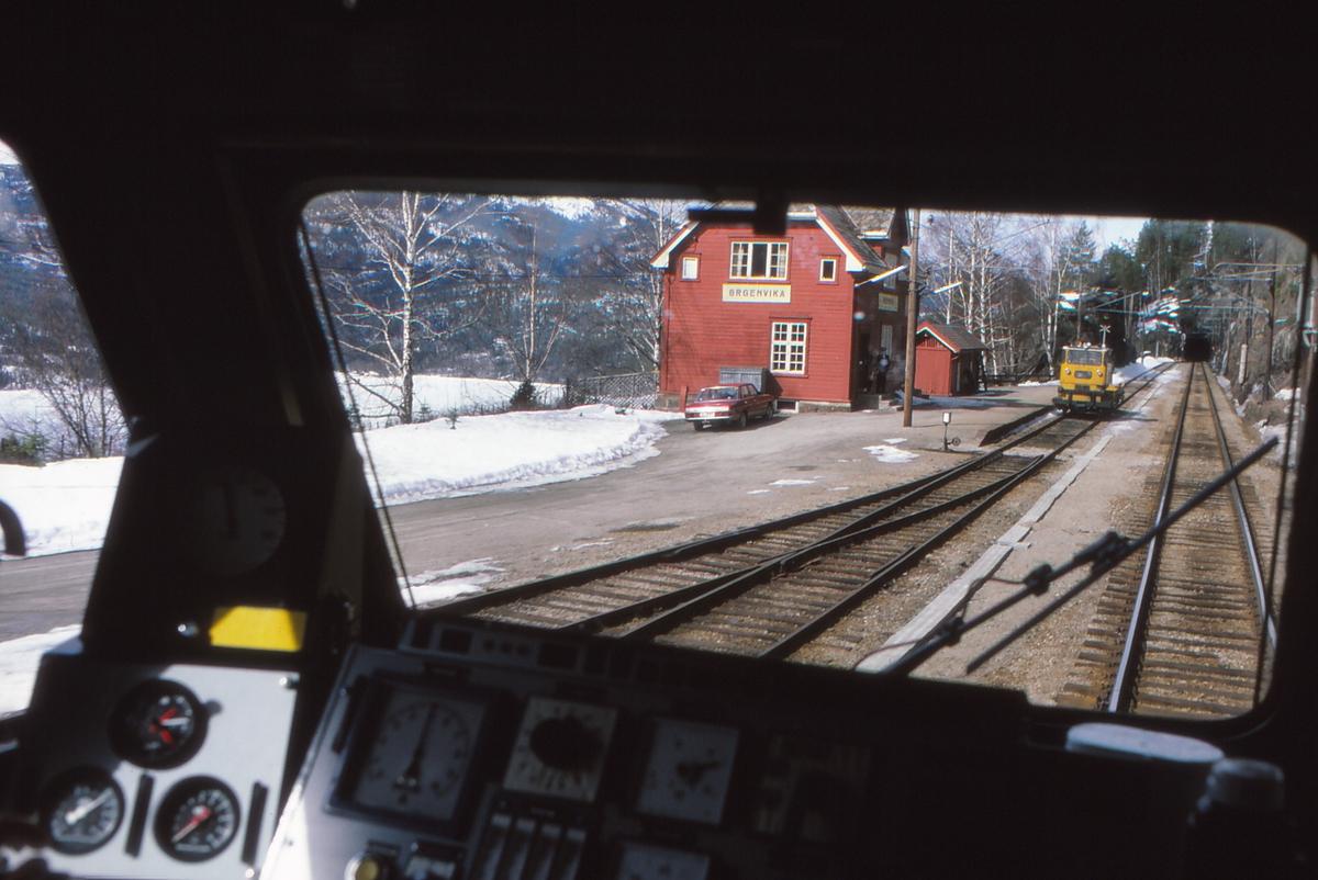 Kryssing i Ørgenvika stasjon sett fra et lokomotiv type El 16. Togekspeditøren (txp) står på trappa. Arbeidet med ny Trolldalen stasjon i forbindelse med utbygging av fjernstyring på Bergensbanen pågikk, og vi kan se nytt forsignal til innkjørhovedsignal A Trolldalen. Krysset betyr at signalet er ugyldig (ikke tatt i bruk), men det er tent for prøving.
