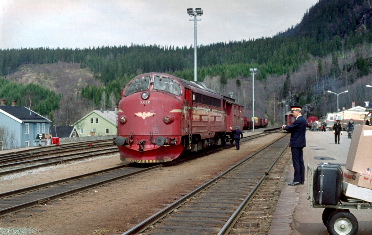 Grong stasjon. Togfører i underveisgodstog 5772 (Mosjøen - Trondheim) har fått avgangsordre av togekspeditøren (txp), og er på vei mot konduktørvogna for å gi avgangssignal til lokomotivfører. Txp sjekker klokken for å kunne notere korrekt tid i togmeldingsboken.