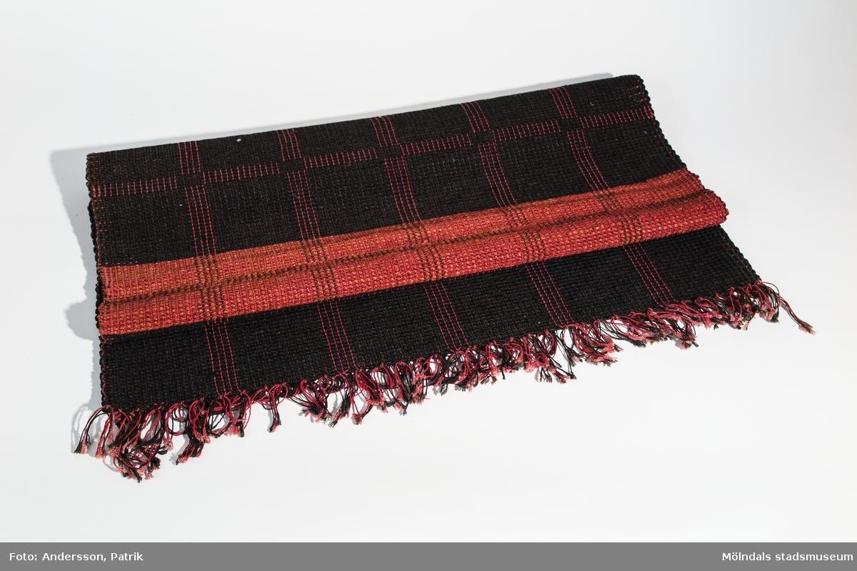 Matta vävd i grovt garn av Johanna Eklund.  Johanna Eklund föddes 1846 och växte upp i Rödbo på norra Hisningen. Hon gifte sig med skolläraren Anton Eklund och bosatte sig i Lindome 1860. När Johannas man gick i pension 1890 köpte de en gård på Flatön i Bohuslän. Med sig hade de allt bohag varav flertal Lindomemöbler, men även textiliär, däribland denna matta.