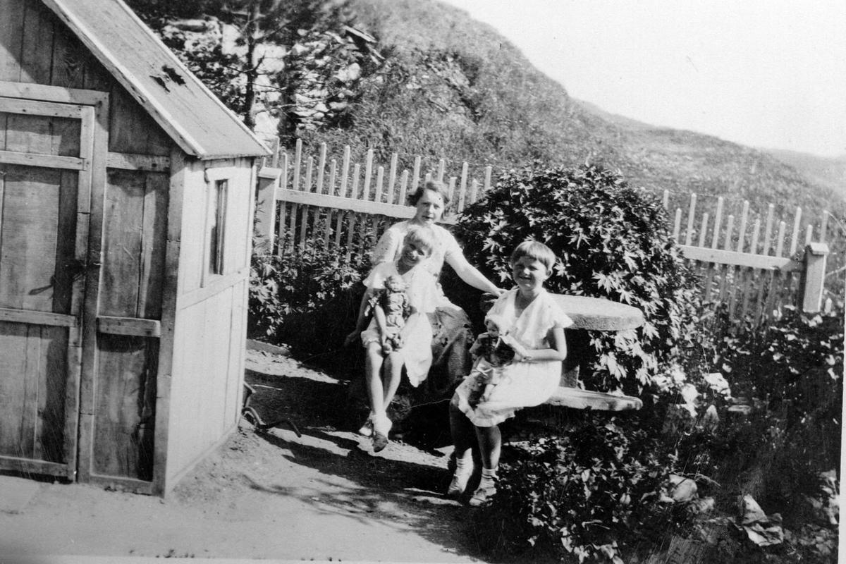 Valborg Schneider med døtre, fotografert i hagen. Stabburshaugen i Harstadgårdsbakken i bakgrunnen.