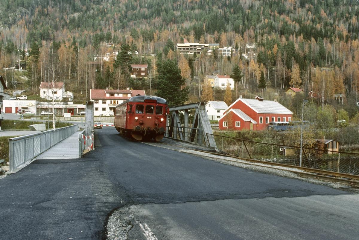 Tog til Kongsberg kjører ut fra Rødberg over felles bro med vei. NSB dieselmotorvogn BM 86k 15 skal bringe de reisende nedover Numedal.