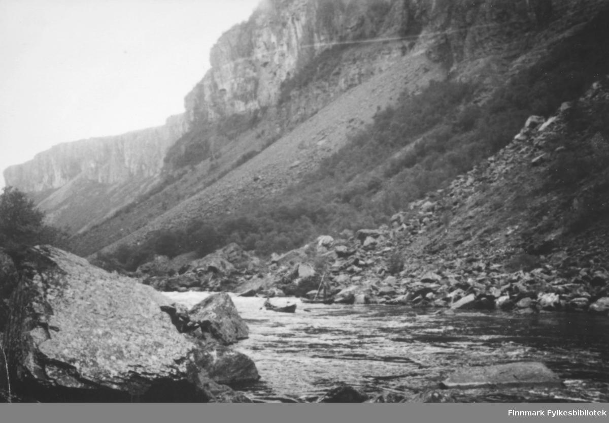 To elvebåter på Altaelva. En mann står og staker i den ene båten. Steiner og skråninger med noe skog utgjør elvebredden
