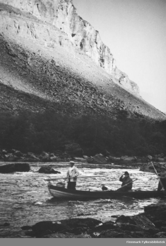 Elvebåtståking i Altaelva. Vi ser tre menn i en elvebåt. I bakgrunnen ser vi en bratt skråing som øverst går over i en steil dalside. Ca.1950-60.
