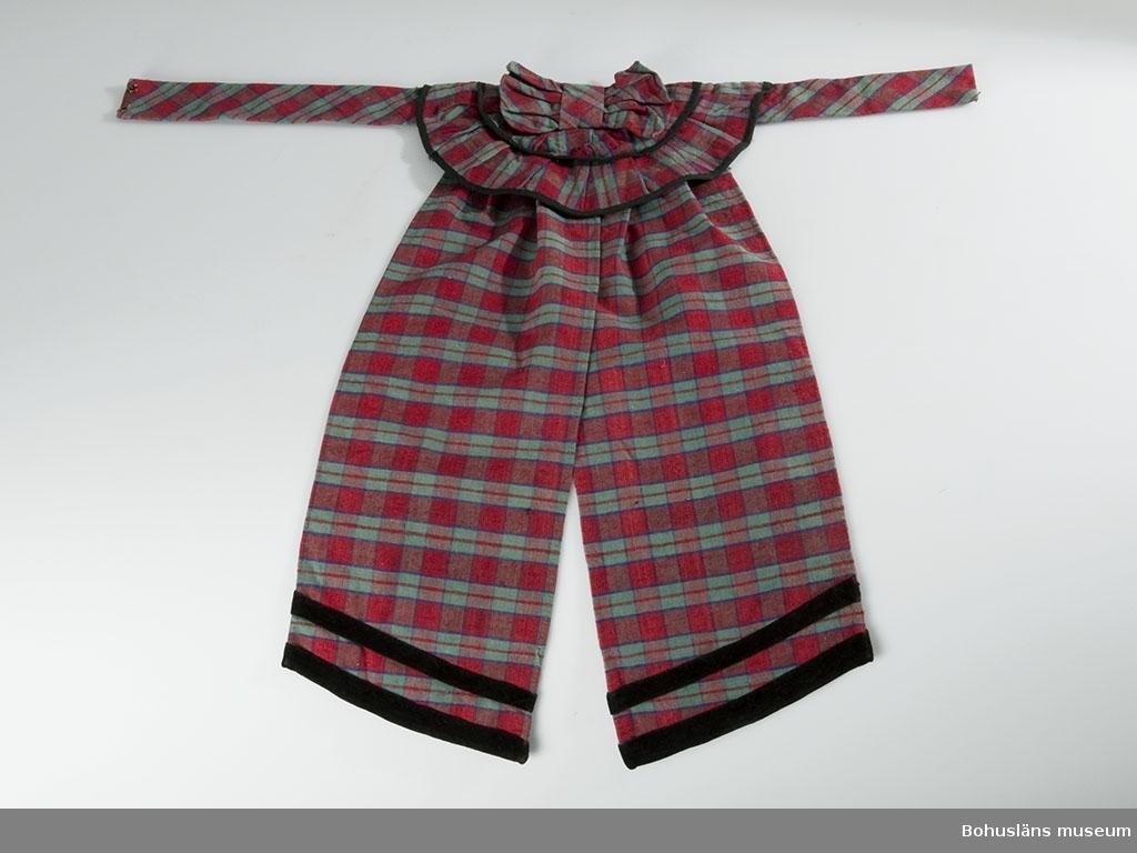 Rutig i rött, grönt och blå-rött. Rynkad baktill. Ylleband i blåtonat rött i nederkanten. En rosett med volanger och långa, breda hängande band är monterad på ett löst skärp som placeras runt midjan med rosetten bak. På volangerna och bandens kanter är det svarta band som dekoration. Fodrat med brun bomull.  Historik om brukaren; se UM026412.
