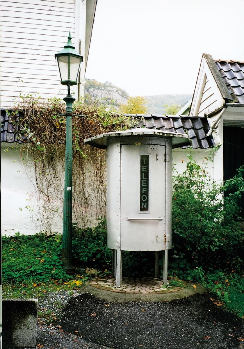 """Kiosken har tilhørt Bergen telefonkompagni. Den er flyttet til Gamle Bergen. Denne kiosktypen ble utformet som en rund metallboks av eloksert aluminium med fire bein, og var åpen nederst. Kiosken fikk kallenavnet """"Sputnik"""", og var tilpasset lokale forhold, var regnet som vedlikeholdsfri, og skulle motstå hærverk. De føste eksemplarene ble satt ut på slutten av 1930-tallet. Seks stykker var i bruk i 1941."""