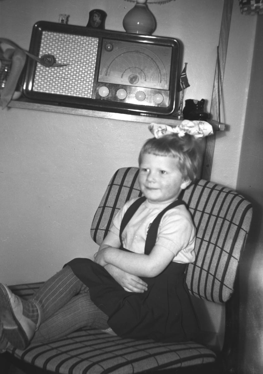 En liten jente sitter i en stol og en Radionette radio står på en liten hylle bak henne. Navn og sted er ukjent.