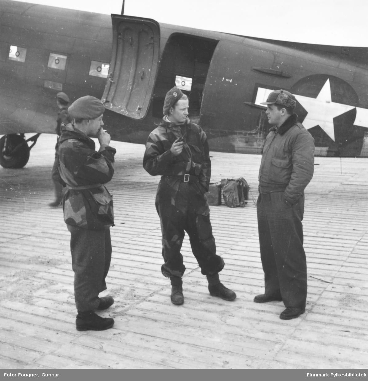 På Banak flyplass. Tre menn står og prater, to er soldater i uniform. Bak mennene står et militærfly, en C-47, Dakota.