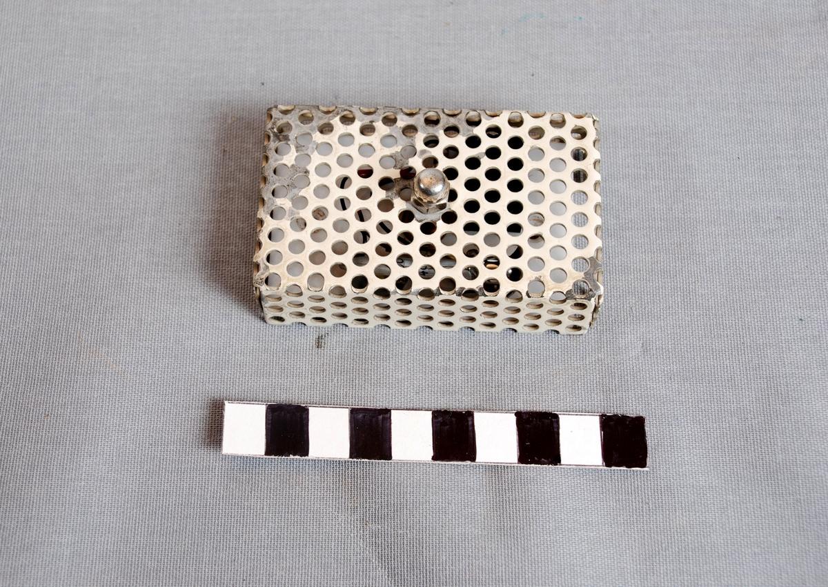 Rektangulær boks der lokket er av gjennomhullet metall og bunnen av hvit hard plast. Lokket er skrudd til bunnen med en skrue midt pålokket. Kontaktken er bruk for varsling ved temperaturstigning, og brukt ved private brannalarmanlegg. Bunnen fungerer som koblingsplate for ledninger og kontakter i boksen.